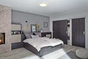 Schlafzimmer mit Kleiderschrank, der mit Schiebetüren versehen ist