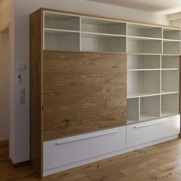 schlichtes Wohnraum-Möbel mit offenen Regalen, Großraumschubladen und einem versteckten Fernseher hinter einer Schiebetür in Eiche