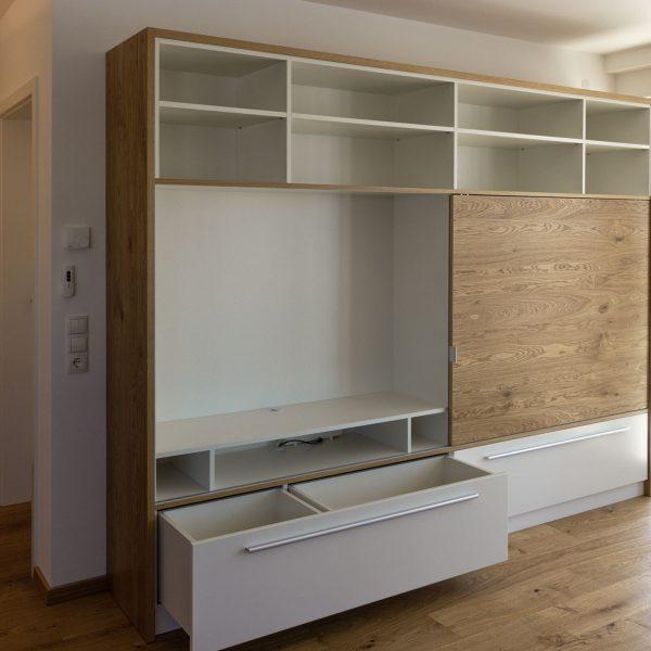 Wohnzimmer-Regal in Eiche und weiß, mit Schubladen und einer Schiebetür vor dem TV-Fach